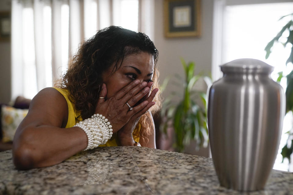 Daphne Bolton wipes away tears as she looks at an urn containing the ashes of her brother at her home on Monday, May 31, 2021, in Charlotte, N.C. Bolton's brother, Johnny Lorenzo Bolton, a 49-year-old Black man was shot shoot to death by a Cobb County Sheriff's Office SWAT team member serving a search warrant last December. (AP Photo/Chris Carlson)