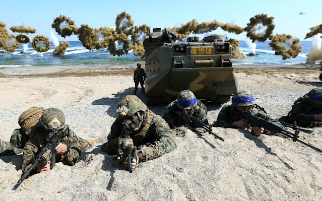 US Marines, left, and South Korean Marines, wearing blue headbands on their helmets, take positions after landing on the beach during a joint military exercise in 2016 - AP