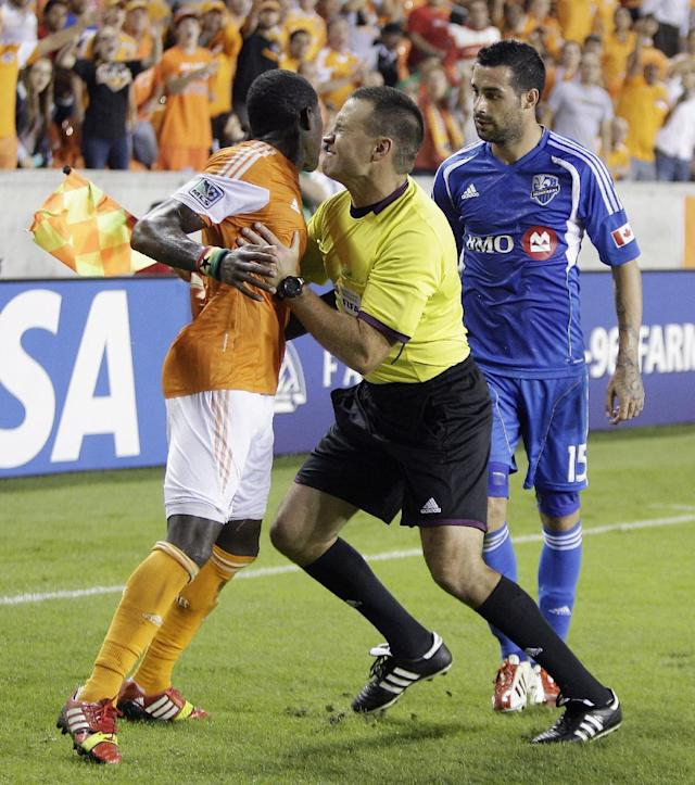 A linesman steps between Houston Dynamo defender Kofi Sarkodie (8) and Montreal Impact forward Andres Romero (15) after Romero kicked Sarkodie after the play was blown dead during a knockout-round match in the MLS Cup soccer playoffs, Thursday, Oct. 31, 2013, in Houston. Houston won 3-0. (AP Photo/Bob Levey)