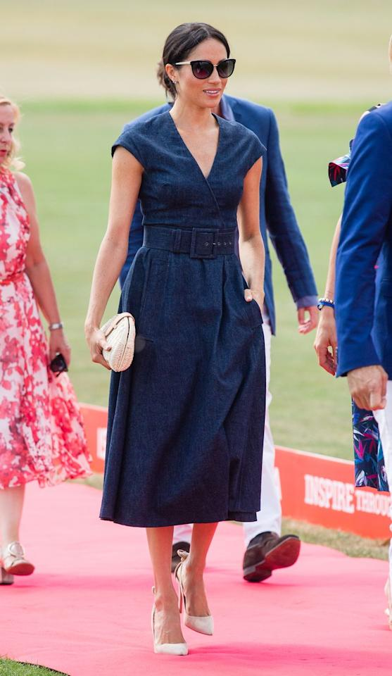 "<p>For a casual day watching Prince Harry play polo, Meghan chose a belted navy blue Carolina Herrera dress, and paired it with statement sunglasses, nude pumps, and an affordable rattan clutch from J.Crew.</p><p><a class=""body-btn-link"" href=""https://go.redirectingat.com?id=74968X1596630&url=https%3A%2F%2Fwww.jcrew.com%2Fp%2Fwomens_category%2Fhandbags%2Fstraw%2Ffan-rattan-clutch%2FJ0146&sref=https%3A%2F%2Fwww.townandcountrymag.com%2Fstyle%2Ffashion-trends%2Fg3272%2Fmeghan-markle-preppy-style%2F"" target=""_blank"">Shop the Clutch</a><br></p>"