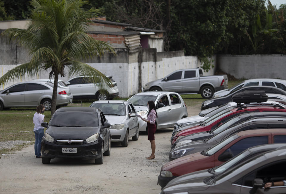 Couples wait inside their cars for their drive-thru weddings outside the registry office in the neighborhood of Santa Cruz in Rio de Janeiro, Brazil, Thursday, May 28, 2020. Couples unable to have a traditional wedding because of the coronavirus pandemic are now taking part in drive-thru weddings. (AP Photo/Silvia Izquierdo)