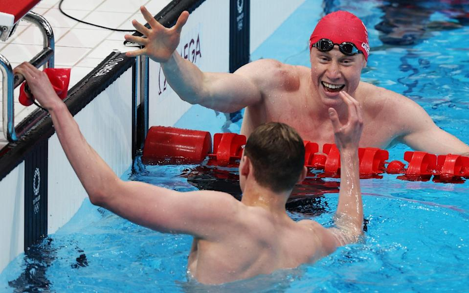 Tom Dean of Team Great Britain shakes hands with Duncan Scott of Team Great Britain after winning the gold medal in the Men's 200m Freestyle Final on day four of the Tokyo 2020 Olympic Games at Tokyo Aquatics Centre on July 27, 2021 in Tokyo, Japan. - GETTY IMAGES