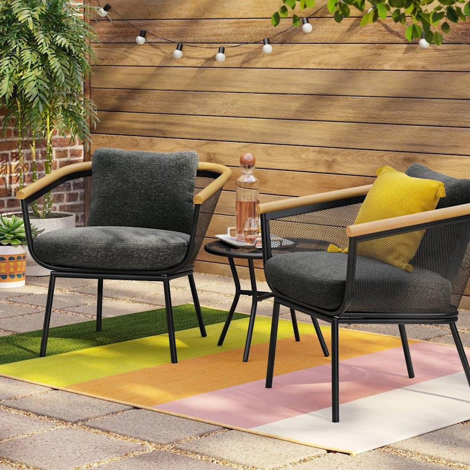 <p>We love the contrast between the wood arms and dark frame on the <span>Bangor Metal Mesh and Faux-Wood Patio Chat Set</span> ($400).</p>