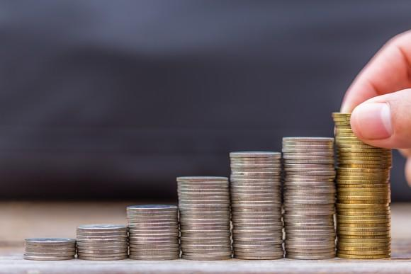 A row of progressively taller stacks of coins, suggestive of a rising stock chart. A hand places a coin on the tallest stack.