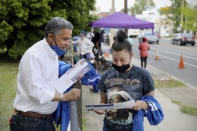 Philadelphia District Attorney candidate Carlos Veg, left, gives a campaign pamphlet to Keila Cruz, of North Philadelphia, during an anti-violence rally at Clara Muhammad Square in West Philadelphia on Saturday, May 15, 2021. Vega is running against incumbent Larry Krasner in the Democratic primary May 18. (Tim Tai/The Philadelphia Inquirer via AP)