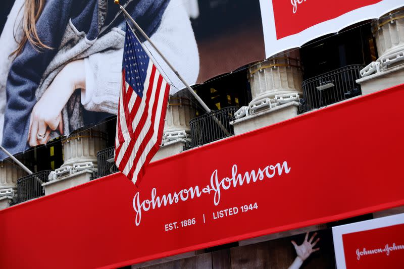 FILE PHOTO: The U.S. flag is seen over the company logo for Johnson & Johnson to celebrate the 75th anniversary of the company's listing at the NYSE in New York