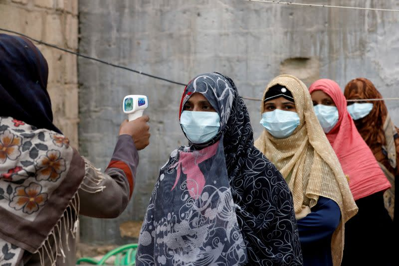 FILE PHOTO: Vaccinators get their temperature checked during an anti-polio campaign in Karachi