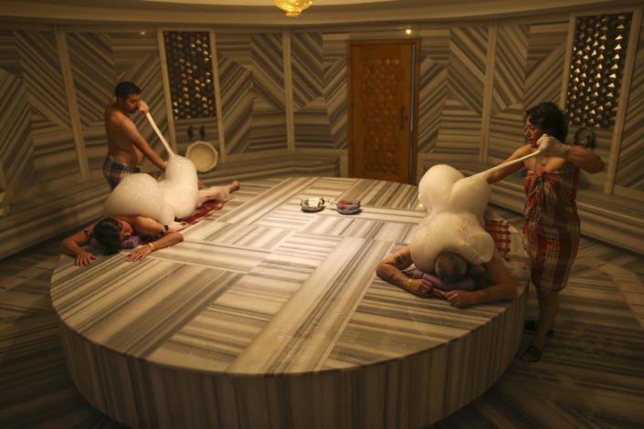 German couple Renate Malzahn and her husband, Harry Malzahn enjoy a Turkish bath in Antalya, southern Turkey, Saturday, June 19, 2021. Hotels in Turkey's Antalya region, a destination beloved by holidaymakers, are preparing to finally resume operations as they expect the return of international tourists after months of setbacks caused by the pandemic that halted travel. (AP Photo/Emrah Gurel)