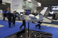 FILE PHOTO: Visitors walk next to model of Dassault Falcon 2000 MRA aircraft during Doha International Maritime Defence Exhibition