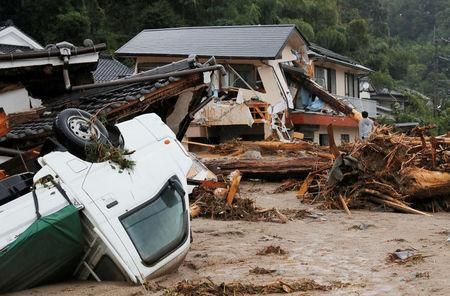 Houses and a vehicle are damaged by a swollen river after heavy rain hit the area in Asakura