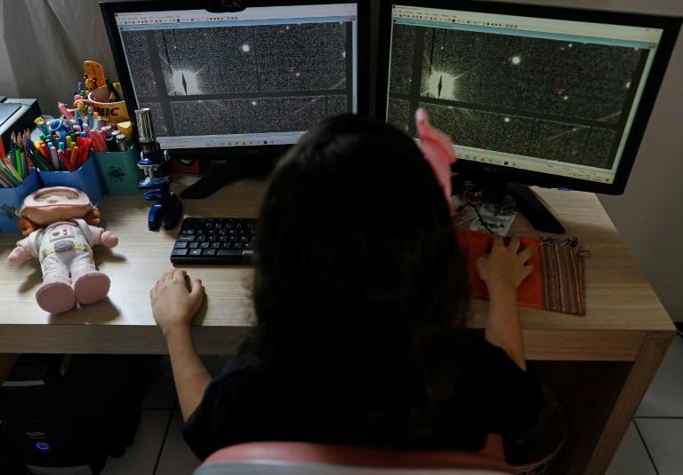 Brazilian 8-year-old astronomer Nicole Oliveira works on her computer at her house trying to discover asteroids as part of a NASA-affiliated educational program (AFP/Jarbas Oliveira)