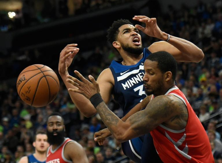 Trevor Ariza #1 of the Houston Rockets fouls Karl-Anthony Towns of the Minnesota Timberwolves as the Rockets moved to the brink of a Western Conference first round playoff series victory with a 119-100 rout