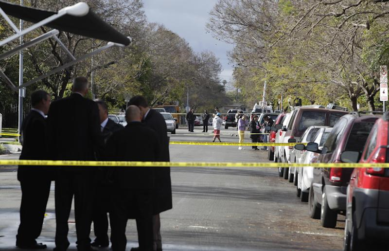 Los Angeles Police Department investigators gather near a command post at the scene of a shooting of two USC students in Los Angeles on Wednesday, April 11, 2012. Police said a gunman opened fire on a BMW near the University of Southern California campus on Wednesday, killing two international students from China in what may have been a bungled carjacking attempt. (AP Photo/Damian Dovarganes)