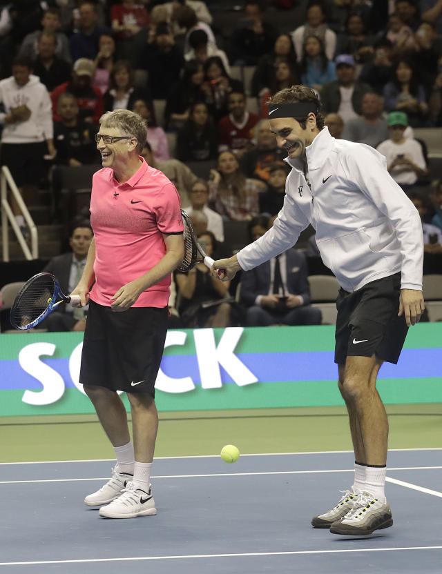 Bill Gates, left, smiles after being hit by a ball during warmups by partner Roger Federer, of Switzerland, before they played in an exhibition tennis match against Jack Sock and Savannah Guthrie in San Jose, Calif., Monday, March 5, 2018. (AP Photo/Jeff Chiu)