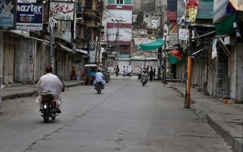 Motorcyclists ride through a market which is closed due to a strike in Rawalpindi, Pakistan, Saturday, July 13, 2019. Pakistani traders have largely kept their business shut across the country against the new sales tax regime in the first budget of the new government they and opposition parties said came on the diktat of International Monetary Fund in turn of a $6bn bailout package - Credit: Anjum Naveed /AP