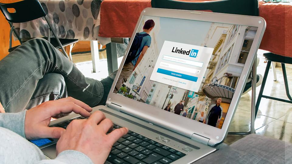 man signing into LinkedIn on laptop