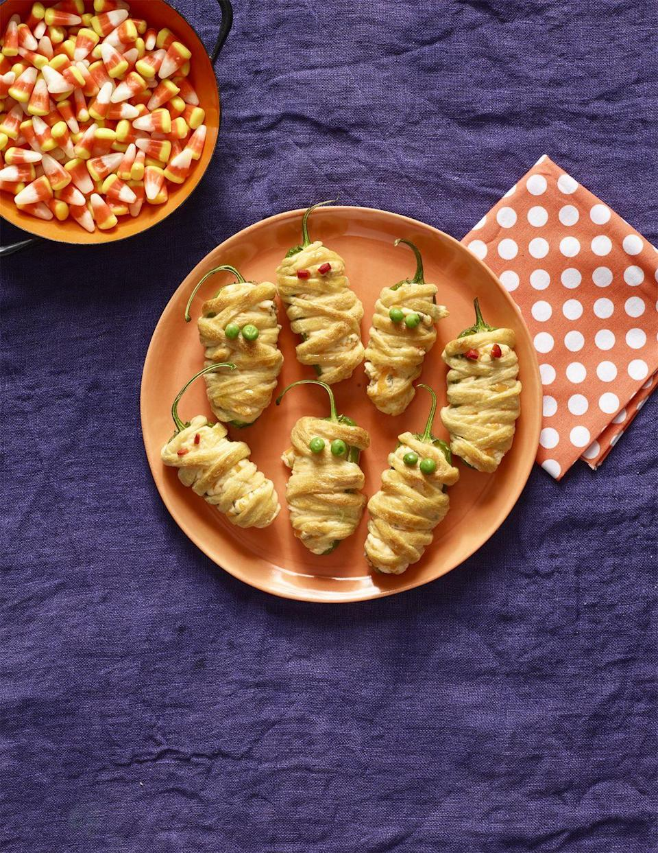 """<p>To make this recipe, wrap jalapeño poppers with puff pastry and add roasted red pepper for eyes.</p><p><a href=""""https://www.womansday.com/food-recipes/food-drinks/recipes/a56191/hot-pepper-mummies-recipe/"""" rel=""""nofollow noopener"""" target=""""_blank"""" data-ylk=""""slk:Get the Hot Pepper Mummies recipe."""" class=""""link rapid-noclick-resp""""><em>Get the Hot Pepper Mummies recipe.</em></a></p>"""
