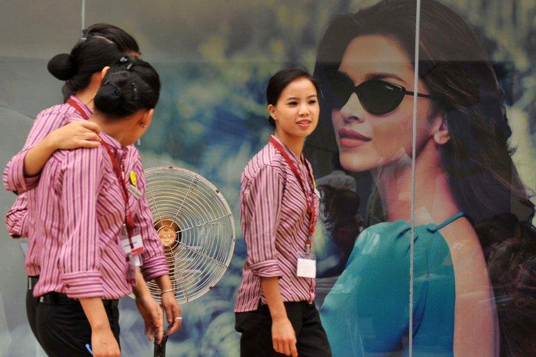 Indian shopping mall employees walk past a billboard in Siliguri on April 15, 2013. Dynamic growth and an expanding middle class are making Southeast Asian consumers among the most confident in the world when it comes to their economic prospects, a survey shows