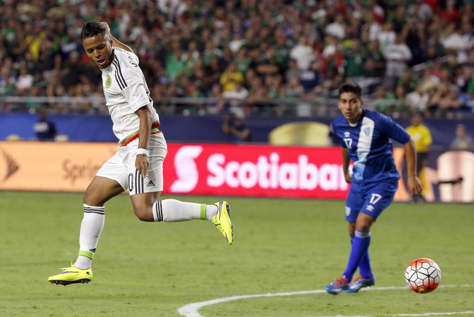 Mexico forward Giovani Dos Santos, left, passes the ball behind him, past Guatemala midfielder Brandon De Leon (17) during the second half of a CONCACAF Gold Cup soccer match Sunday, July 12, 2015, in Glendale, Ariz. The game ended in a 0-0 tie. (AP Photo/Ross D. Franklin)