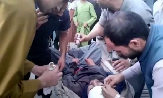 People tend to a wounded man near the site of a deadly explosion outside the airport in Kabul, on Thursday. Two suicide bombers and gunmen targeted crowds massing near the airport in the waning days of a massive airlift that has drawn thousands of people seeking to flee the Taliban.  (The Associated Press - image credit)