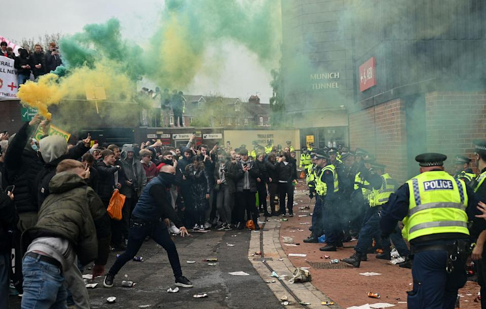Police try to move people away from the stadium after a supporter's protest against Manchester United's ownersAFP