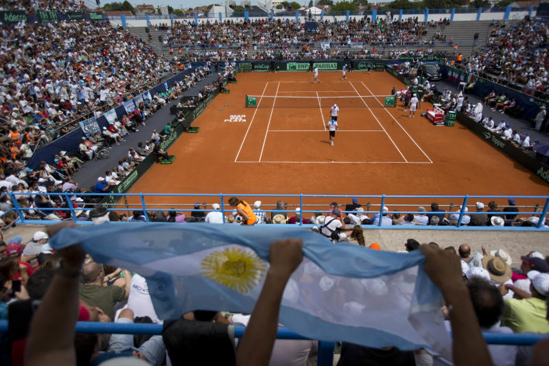 Argentina tennis fans wave an Argentine flag as they cheer for their team playing a Davis Cup doubles tennis match against Italy in Mar del Plata, Argentina, Saturday, Feb. 1, 2014. (AP Photo/Eduardo Di Baia)