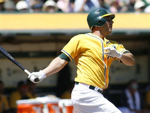 Oakland Athletics' George Kottaras follows through on a two-run home run against the Los Angeles Angels in the second inning of a baseball game in Oakland, Calif., Wednesday, Aug. 8, 2012. (AP Photo/Dino Vournas)