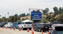 Cars wait in line at a COVID-19 testing center at Dodger Stadium in Los Angeles on June 25