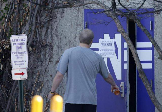 An unidentified Northwestern football player walks into McGaw Hall, past a polling place sign and parking space for head coach Pat Fitzgerald, where voting is taking place on the student athlete union question Friday, April 25, 2014, in Evanston, Ill. Northwestern football players cast secret ballots Friday in an on-campus hall adjacent to their home stadium on whether to form the nation's first union for college athletes. (AP Photo/Charles Rex Arbogast)