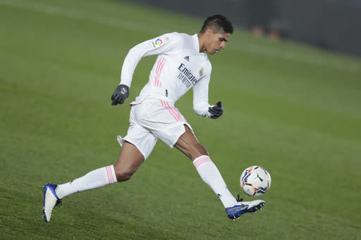 Real Madrid's Raphael Varane runs with the ball during the Spanish La Liga soccer match between Real Madrid and Granada at the Alfredo Di Stefano stadium in Madrid, Spain, Wednesday, Dec. 23, 2020. (AP Photo/Bernat Armangue)