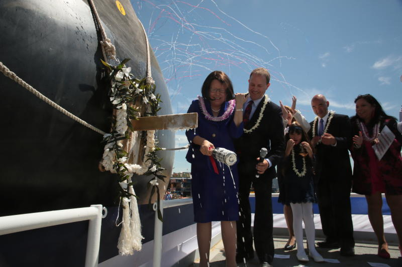 This photo provided by Bath Iron Works shows Irene Hirano Inouye smiles after breaking a bottle of Champagne on the bow of a warship bearing the name of her late husband, Hawaii Sen. Daniel Inouye, during a ceremony at Bath Iron Works on Saturday, June 22, 2018, in Bath, Maine. (Dennis Griggs/Bath Iron Works via AP)