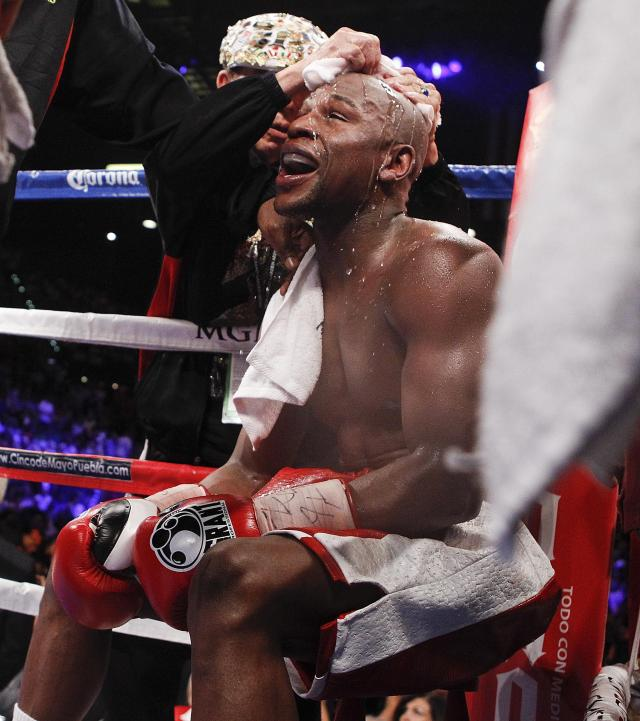 """FILE - In this Saturday, May 5, 2012 file photo, Floyd Mayweather Jr. is doused with water in his corner between rounds during a WBA super welterweight title fight against Miguel Cotto, in Las Vegas. The head of the British Boxing Board of Control said Wednesday May 6, 2020, the body was working on an """"apparatus"""" that would allow fighters to safely spit out water as they catch their breath between rounds. It's among dozens of protective measures under discussion under a plan to protect fighters from the coronavirus when boxing resumes in Britain, possibly in July. (AP Photo/Eric Jamison, File)"""