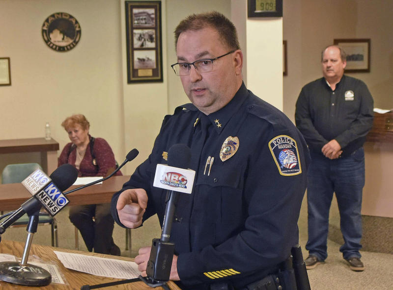 Mandan Police Chief Jason Ziegler announces an arrest in a quadruple homicide at a press conference Thursday night, April 4, 2019, in Mandan, N.D. In back are Deputy Police Chief Lori Flaten, left, and Mandan Mayor Tim Helbling. Police in North Dakota say they've arrested a 44-year-old man in the slayings of four people earlier this week at a business in Mandan. Ziegler says surveillance video identified a vehicle of interest and helped lead them to the suspect, who lived in the small town of Washburn about 35 miles (56 kilometers) north of Mandan. (Tom Stromme/The Bismarck Tribune via AP)
