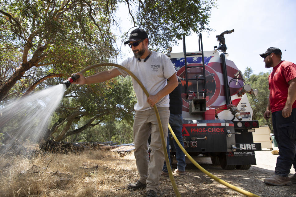 In this July 28, 2021 image provided Perimeter Solutions, Eric Clancy, left, applies a new type of long-lasting fire retardant at former President Ronald Reagan's coastal mountain ranch in the Santa Ynez mountains near Santa Barbara, Calif. U.S. officials on Tuesday, Oct. 5, 2021, approved Perimeter Solutions' new fire retardant that could significantly aid in fighting increasingly destructive wildfires. (Perimeter Solutions Photo via AP)