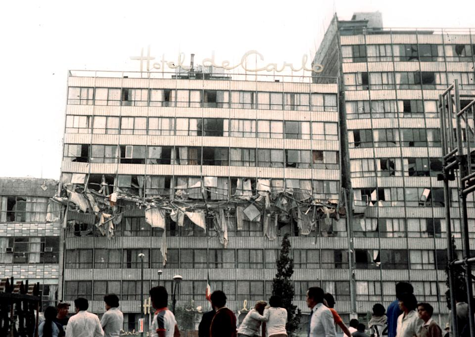 People look at the damaged Hotel De Carlo in Revolution Plaza in Mexico City