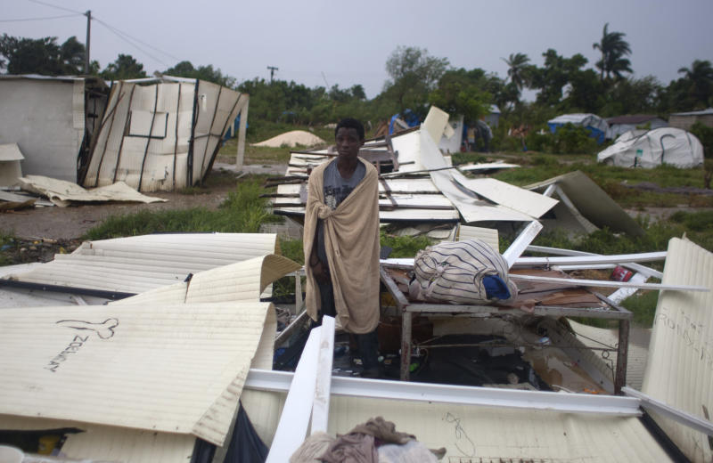 A man stands next to his bed after Tropical Storm Isaac destroyed his home and others at a camp set up for people displaced by the 2010 earthquake in Port-au-Prince, Haiti, Saturday, Aug. 25, 2012. Tropical Storm Isaac swept across Haiti's southern peninsula early Saturday, dousing a capital city prone to flooding and adding to the misery of a poor nation still trying to recover from the 2010 earthquake. (AP Photo/Dieu Nalio Chery)