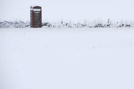 A phone box stands in snow in Newhaven, central England, January 21, 2015. REUTERS/Darren Staples/File Photo