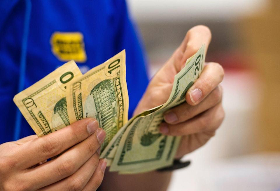 A Best Buy Co. employee counts U.S. twenty and ten dollar banknotes at a Best Buy Co. store ahead of Black Friday in San Francisco, California, U.S. (Photo: David Paul Morris/Bloomberg via Getty Images)