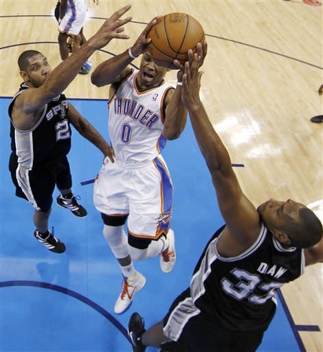 Oklahoma City Thunder point guard Russell Westbrook (0) shoots under pressure from San Antonio Spurs center Tim Duncan (21) and power forward Boris Diaw (33), of France, during the first half of Game 6 in the NBA basketball Western Conference finals, Wednesday, June 6, 2012, in Oklahoma City. (AP Photo/Jim Young, Pool)