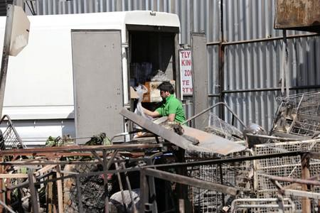 A shop keeper examines damaged property after overnight unrest and looting in Alexandra township, Johannesburg