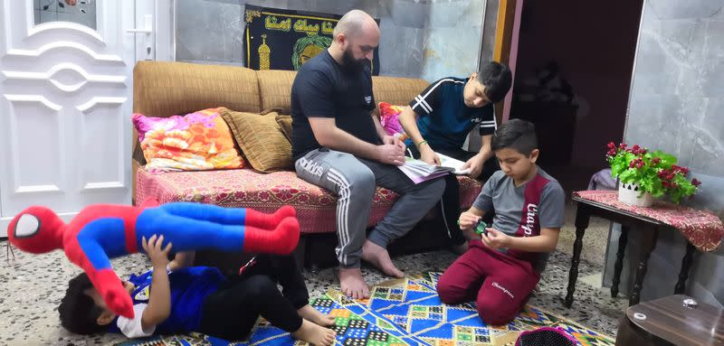 Local worker Muhammad Subeih Haider plays with his children at his home in Basra