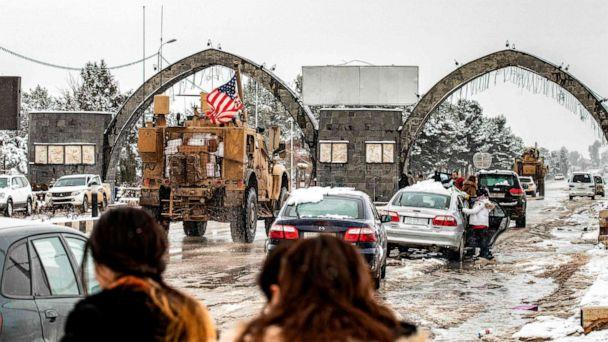 PHOTO: People look at a U.S. military patrol passing by other cars in the snow-covered northeastern Syrian town of al-Malikiyah at the border with Turkey on Feb. 10, 2020. (Delil Souleiman/AFP via Getty Images)