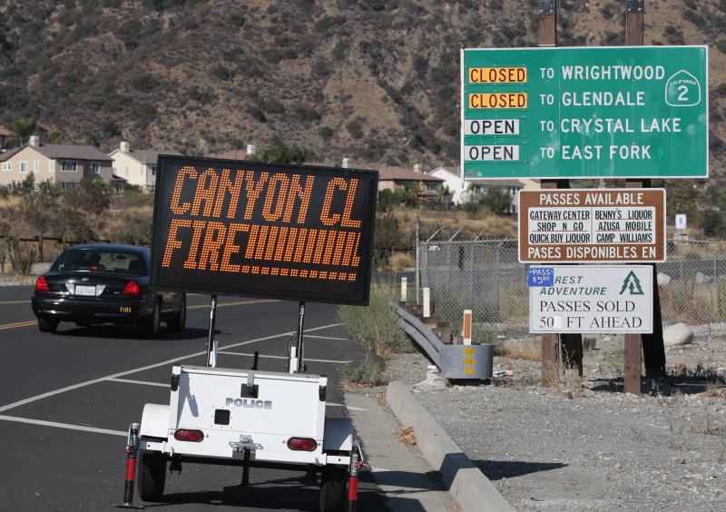 A sign on San Gabriel Canyon Road warns of a street closure as firefighters fight a wildfire in the Angeles National Forest north of Glendora, Calif. Monday, Sept. 3, 2012. A day after the wildfire broke out near a campground and forced the evacuation of thousands of campers and picnickers it had grown to more than 4,100 acres, or roughly 6 square miles, and was just five percent contained. (AP Photo/Jason Redmond)