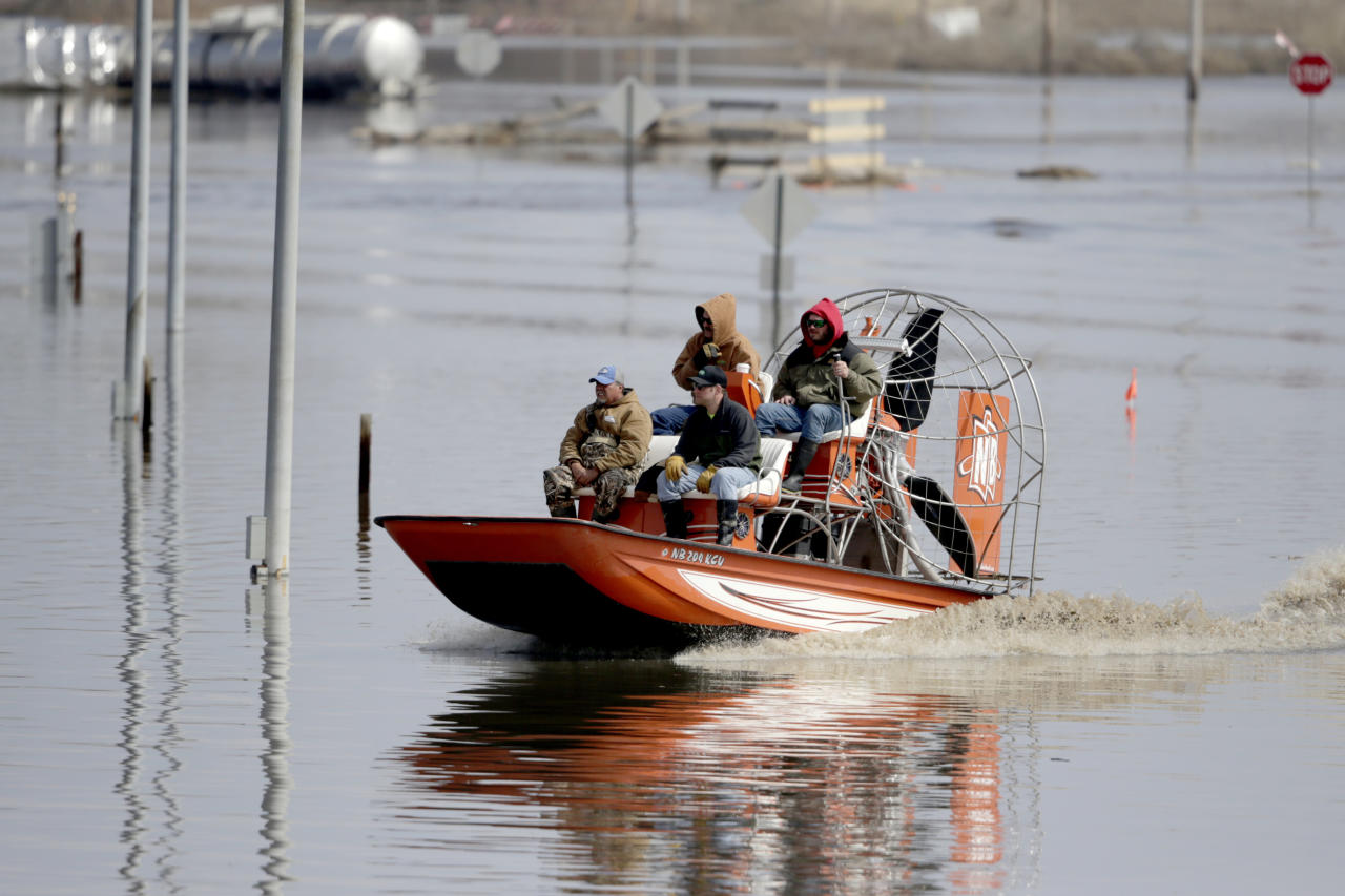 Gabe Schmidt, owner of Liquid Trucking, back right, travels by air boat with Glenn Wyles, top left, Mitch Snyder, bottom right, and Juan Jacobo, bottom left, as they survey damage from the flood waters of the Platte River, in Plattsmouth, Neb., Sunday, March 17, 2019. Hundreds of people remained out of their homes in Nebraska, but rivers there were starting to recede. The National Weather Service said the Elkhorn River remained at major flood stage but was dropping. (AP Photo/Nati Harnik)