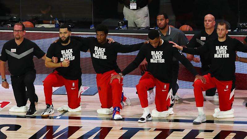 The Toronto Raptors are pictured kneeling during the national anthem prior to their playoff game against Brooklyn.