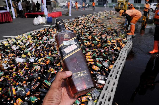 <p>Thousands of alcoholic beverages from unlicensed sellers are destroyed at Polda Metro Jaya, May 23, 2017. Indonesian police conduct the destruction of alcoholic beverages ahead of Ramadhan and Idul Fitri celebrations anticipate the high number of crime caused by alcohol. (Photo: Dasril Roszandi/NurPhoto via Getty Images) </p>
