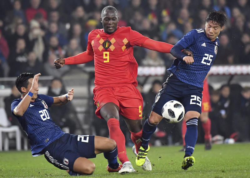 Belgium's Romelu Lukaku, center, battles for control of the ball with Japan's Kazuki Nagasawa, right, during a international friendly soccer match between Belgium and Japan at the Jan Breydel Stadium in Brugge, Belgium, Tuesday, Nov. 14, 2017. (AP Photo/Geert Vanden Wijngaert)