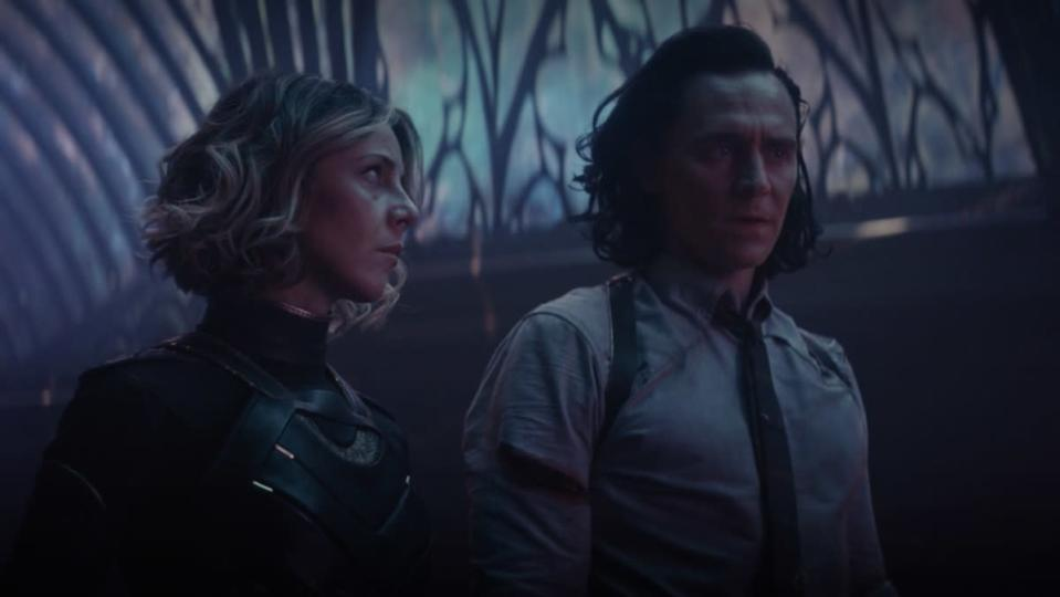 Sylvie looks at Loki in a room with purple lights