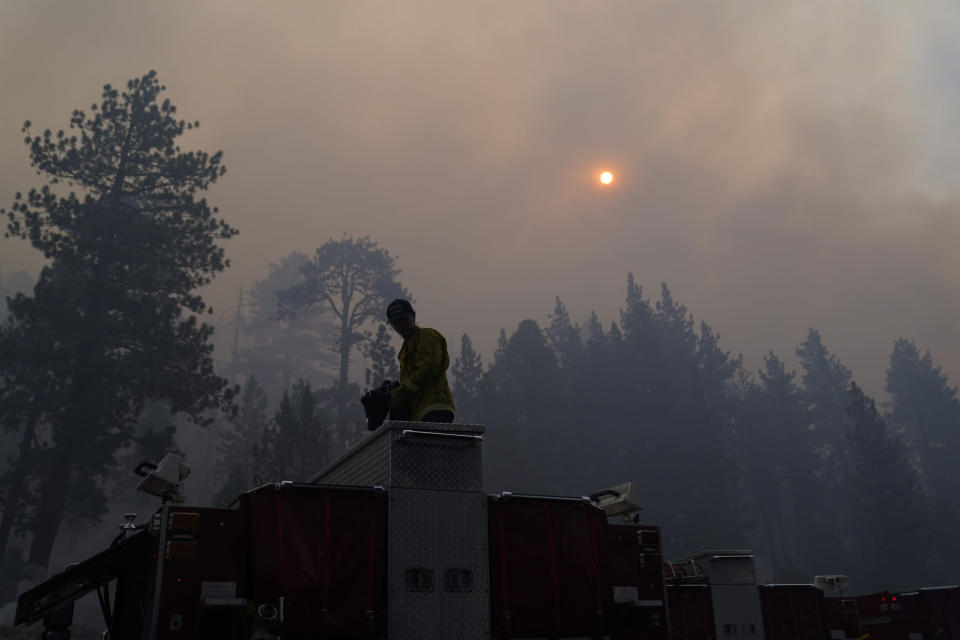 Firefighter Walter Villalobos from Cosumnes Fire Department stands on top of a fire truck as the sun is visible through smoke generated by the Caldor Fire near South Lake Tahoe, Calif., Friday, Sept. 3, 2021. Fire crews took advantage of decreasing winds to battle a California wildfire near popular Lake Tahoe and were even able to allow some people back to their homes but dry weather and a weekend warming trend meant the battle was far from over. (AP Photo/Jae C. Hong)