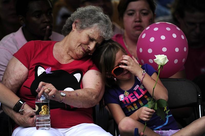 "Family members of the victims of the Century 16 theater shooting remember their loved ones during a vigil at the Aurora Municipal Center campus in Aurora, Colo. Sunday, July 22, 2012. 12 people were killed and 58 were injured in a shooting during an early Friday premiere of ""The Dark Knight Rises."" (AP Photo/The Denver Post, AAron Ontiveroz, Pool)"